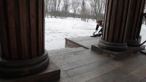 Bearded Russian in the 19ntury, shines shoes on the porch, wooden columns Footage