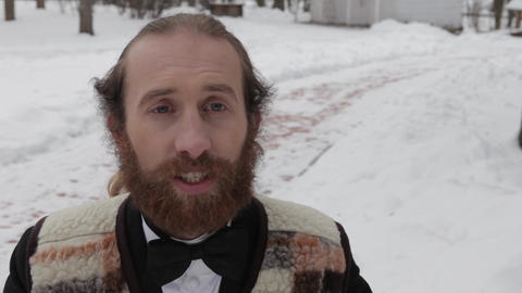 movie clapper, bearded man in a suit and bow tie on a background of winter Footage