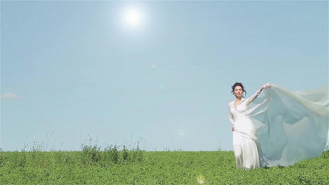 Girl in white dress walking on green field with a shawl which is fluttering in t Footage