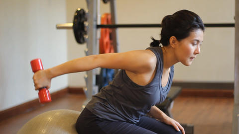 Woman Sitting On The Ball Pulling Dumbbell stock footage