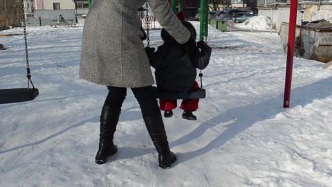 winter afternoon mother with her ​​daughter comes swing Footage