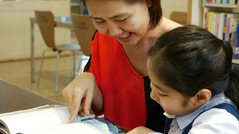 4K UHD : Little Asian students and teacher reading book in library together Footage