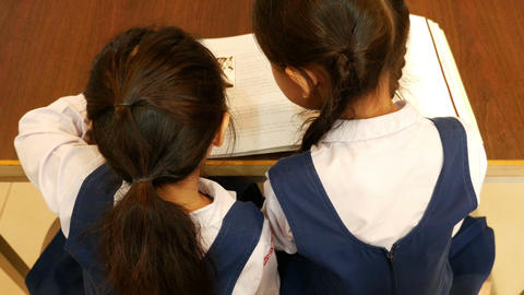 4K UHD : Top view of little Asian students with uniform reading book in library Live Action