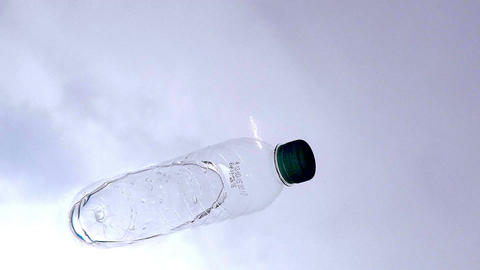 Plastic Bottle Floating Against A Blue Sky From An Underwater Perspective stock footage