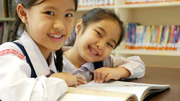 4K Video : Little Asian students wearing uniforms and reading book in library Footage