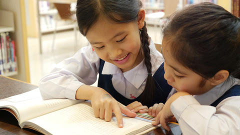 4K UHD : Little Asian students with uniform reading book in library together, ti Footage