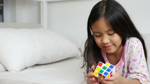 4K Video : Little Asian girls playing rubik cube on the bed Footage