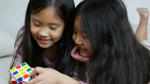 4K Video : Little Asian girls playing rubik cube on the bed together Footage