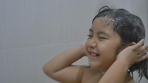 Asian child washes hair in bathroom Footage
