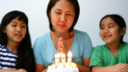 Slow motion happy moment of Asian family blowing birthday candles Footage