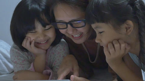 Asian mom lies with her daughters and plays with digital tablet together, Pan sh Footage