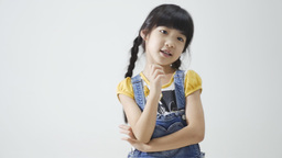 Little Asian girl singing and dancing on white background Footage