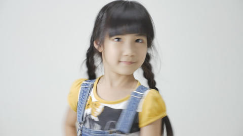 Little Asian girl is smiling on white background Footage