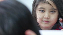 Little Asian girl getting haircut in hair salon : 4K Video Live Action