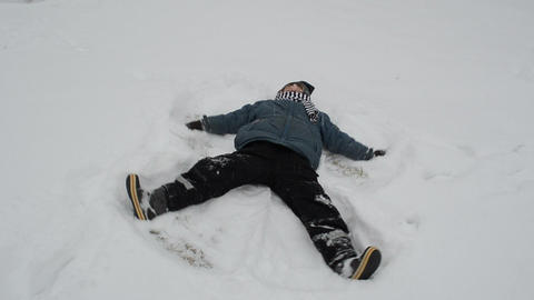 little boy rejoiced winter day and make an snow angel Footage