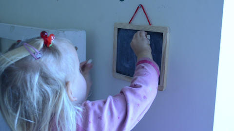 girl rubbing her drawing on a black table Footage