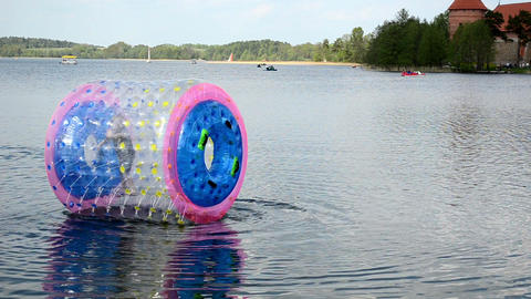 Child In Zorb Ball In Trakai. People Sail Boats Water Bicycle stock footage