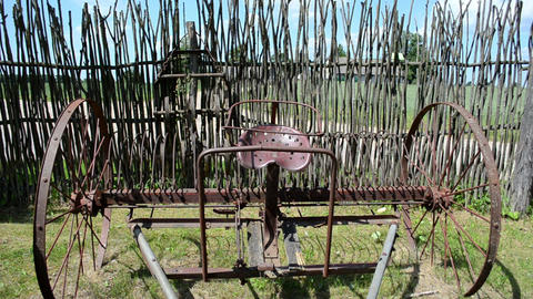 old corroded field harrow tool stand wooden fence Footage