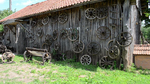 retro carriage cart wheels hang on rural building wall bench Footage