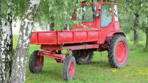 retro red tractor stand near birch trees and branch move in wind Footage