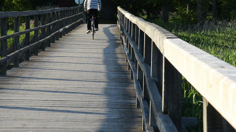 Teenage Teen Male Ride Fast Bicycle On Wooden Bridge In Park stock footage