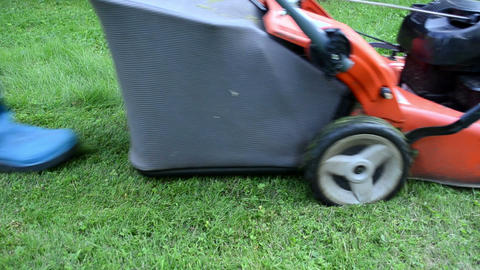 worker in rubber boots drive meadow grass cutter mower Footage