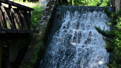 wooden bridge through stream and water fall cascade Footage