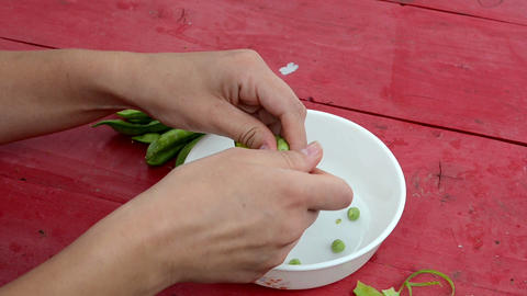 closeup woman hand depod green peas white dish red wooden table Footage