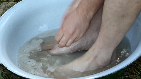 man wash hairy legs in rural bowl water with soap Live Action