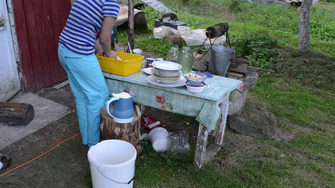 deprived woman wash dirty dishes and cats walk. rural poverty Footage
