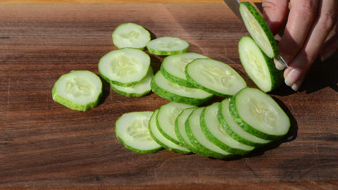 hands cut slice cucumber knife small pieces wooden board Footage