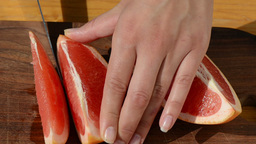 hand slice fresh ripe juicy grapefruit pomelo fruit into pieces Footage