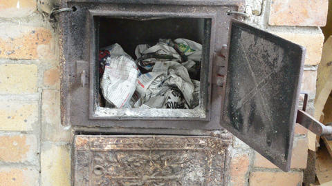 hand put newspaper paper firelighter old rural stove furnace Footage