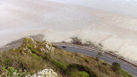 A black car in slow motion, seen from the top, drives along the sea. the camera Footage