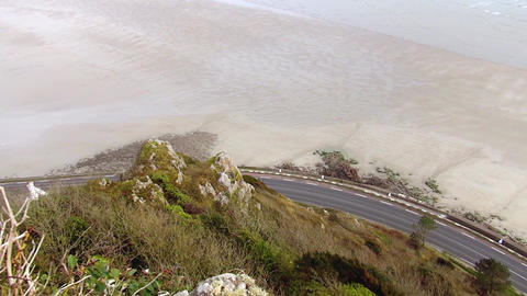 A black car, seen from the top, drives along the sea. the camera is following a Footage