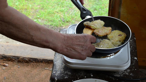 senior women bake potato pancake in rural house kitchen Footage