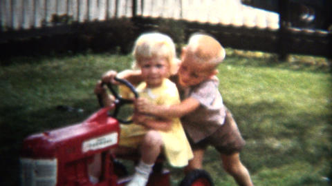 (8mm Vintage) 1954 Brother Pushing Sister Toy Tractor. Iowa, USA Footage