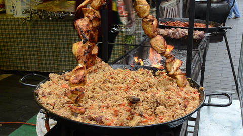 pilaf in outdoor restaurant and meat baking fire Footage