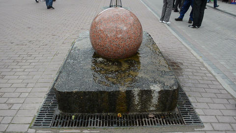 round stone fountain spin water flow pavement people Footage