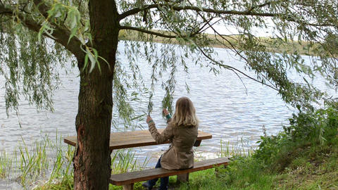 young woman sit bench ripple lake water play willow tree branch Footage