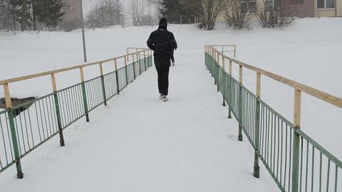 people walk frozen river bridge winter snowstorm snow fall Footage
