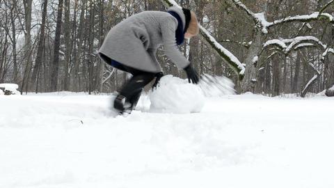 woman roll snowball snow ball coat skirt snowman winter park Footage