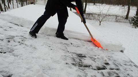 man orange shovel tool clean push snow roof winter Footage