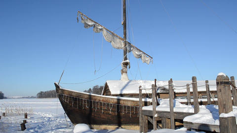 retro wooden ship frozen lake ice pier sail move wind blue sky Footage