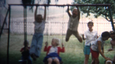 (8mm Vintage) 1962 Kids Wildly Playing On Swingset. Iowa, USA Footage