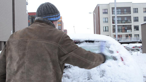 man jacket knit hat cleaning snow car parking flat house winter Footage