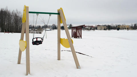 empty colorful swing seat move winter snow beach playground Footage