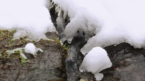 closeup stream brook current flow snow icicles spring Footage