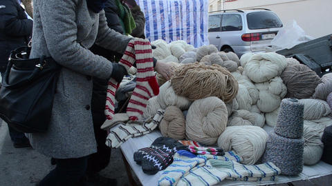 woman pick natural wool thread outdoor spring fair market event Footage