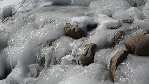 water move frozen brook ice stones winter sunlight reflections Footage